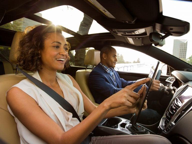 a man and woman driving to birchwood winnipeg car dealership